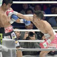 Daigo Higa lands a punch on Mexico's Moises Fuentes during their WBC flyweight world title bout in Naha on Sunday. | KYODO