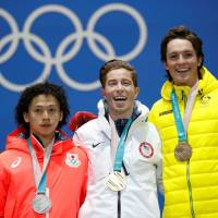 Silver medalist Ayumu Hirano (left) stands with winner Shaun White (center) and bronze medalist Scotty James during Wednesday's medal ceremony for the men's halfpipe. | REUTERS