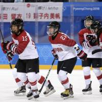 Japan's Rui Ukita (left) celebrates with teammates after scoring a second-period goal in a preliminary round game in Gagneung, South Korea. | AP