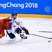 Czech Republic's Tomas Kundratek (left) and Broc Little of the United States battle for the puck in overtime in the men's quarterfinals at the Pyeongchang Games. | AFP-JIJI