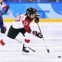 Japan's Miho Shishiuchi moves the puck in the second period against Korea on Wednesday. | KYODO