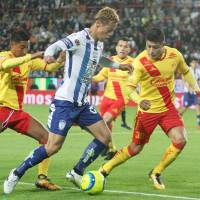 Pachuca's Keisuke Honda takes on the Morelia defense during their Mexican first-division match on Saturday. | KYODO