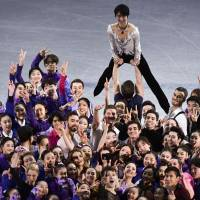 Two-time Olympic champion Yuzuru Hanyu is lifted up as figure skaters and flower girls pose for photographs after Sunday's gala event at the Pyeongchang Games in Gangneung, South Korea. | AFP-JIJI
