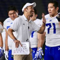 IBM BigBlue head coach Shinzo Yamada, seen celebrating with one of his players after a victory over the Obic Seagulls last September, is excited about the planned relaunch of the XFL in 2020. | KAZ NAGATSUKA
