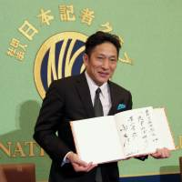 Aoyama Gakuin University men's ekiden coach Susumu Hara poses for photos during a news conference on Monday at the Japan National Press Club. | KAZ NAGATSUKA