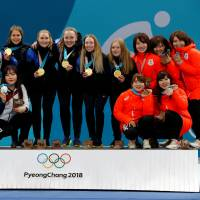Gold medalist Sweden (center) poses with runner-up South Korea (right) and Japan, which finished third, after the women's curling competition on Sunday. | REUTERS