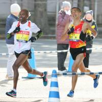 South Africa's Desmond Mokgoba (left) and Hayato Sonoda compete during the Beppu-Oita Marathon on Sunday. | KYODO