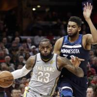 Cleveland's LeBron James drives against Minnesota's Karl-Anthony Towns during the first half of the Cavaliers' overtime victory over the Timberwolves on Wednesday. | AP