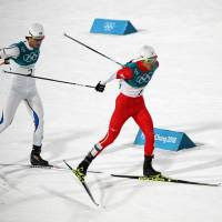 Japan's Akito Watabe (right) skis against Norway's Jarl Magnus Riiber in the Nordic combined men's large hill 10-km event at Alpsenia Cross-Country Skiing Centre on Tuesday night. Watabe finished fifth overall. | REUTERS
