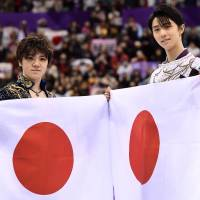 Yuzuru Hanyu (right) and Shoma Uno hold Japanese flags after finishing the competition first and second, respectively. | AFP-JIJI