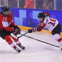 Smile Japan's Haruna Yoneyama (right) and Switzerland's Christine Meier vie for the puck on Tuesday night in the 5th-6th place match on Tuesday night. | AFP-JIJI