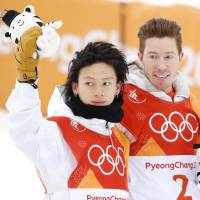 Pyeongchang Olympic men's halfpipe silver medalist Ayumu Hirano waves to the crowd alongside competition winner Shaun White of the United States on Wednesday. | KYODO