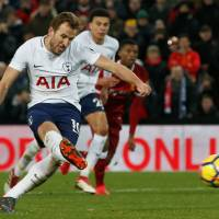 Tottenham's Harry Kane takes a penalty against Liverpool on Sunday in Liverpool, England. The match ended in a 2-2 draw. | REUTERS