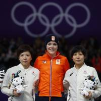 Gold medalist Jorien ter Mors of the Netherlands  (center), runner-up Nao Kodaira (left) and bronze medalist Miho Takagi are seen during the victory ceremony for the women's 1,000-meter speedskating final on Wednesday in Gangneung, South Korea. | REUTERS