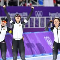 (From left) Japan's Ayano Sato, Miho Takagi and Nana Takagi rejoice after winning the women's team pursuit gold medal in an Olympic record time of 2 minutes, 53.89 seconds on Wednesday night at Gangneung Oval. | AFP-JIJI