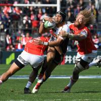 The Sunwolves' Timothy Lafaele (left) and Willie Britz (right) tackle the Brumbies' Christian Lealiifano on Saturday. | AFP-JIJI