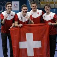 The Swiss team celebrates after beating Canada to win the bronze medal in men's curling on Friday. | AP