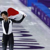 Silver medallist Miho Takagi of Japan holds the national flag after the women's 1,500 meters speedskating race in Gangneung on Monday evening.   AP