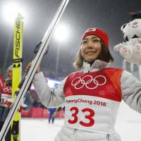 Bronze medalist Sara Takanashi celebrates on the podium alongside gold medalist Maren Lundby during the victory ceremony. | REUTERS