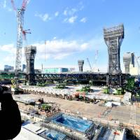 A photographer takes pictures at the construction site of the Olympic Aquatics Centre in Koto Ward, Tokyo, on Tuesday. | YOSHIAKI MIURA