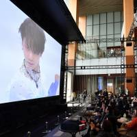Figure skating fans watch a public viewing of the Pyeongchang Olympics men's figure skating competition in Roppongi Midtown on Friday. | YOSHIAKI MIURA