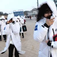 Staff from Olympic Park struggle to walk due to strong winds on Wednesday in Pyeongchang, South Korea. | REUTERS