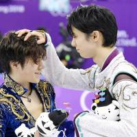 Teammates Shoma Uno (left) and Yuzuru Hanyu share a moment after winning the silver and gold medals of the men's figure skating event.  | KYODO