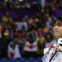 Gold medallist Yuzuru Hanyu of Japan celebrates savors the moment following his victory in the men's single free skating competition.  | REUTERS