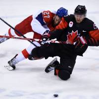 Czech Republic's Martin Ruzicka (left) and Canada's Brandon Kozun fight for the puck during the final period of the men's preliminary round ice hockey match between Canada and Czech Republic. | AFP-JIJI