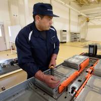 A 4R Energy Corp. employee checks a used lithium-ion electric vehicle battery during a demonstration at a 4R Energy Corp. factory in Namie, Fukushima Prefecture, during a media tour on Monday. | BLOOMBERG