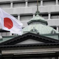A Hinomaru flies outside Bank of Japan headquarters in Tokyo. A survey shows that three-quarters of Japan's companies say the BOJ needs to exit from its radical monetary easing policy but most do not see that happening until next year or beyond. | BLOOMBERG