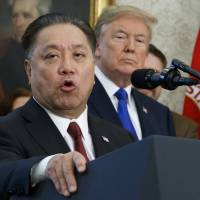 Broadcom CEO Hock Tan speaks while U.S. President Donald Trump listens, during an event at the White House in Washington last November to announce the company is moving its global headquarters to the United States. In a decision announced Monday, Trump is blocking Singapore chipmaker Broadcom from pursuing a hostile takeover of U.S. rival Qualcomm on the grounds that the combination would threaten national security. | AP