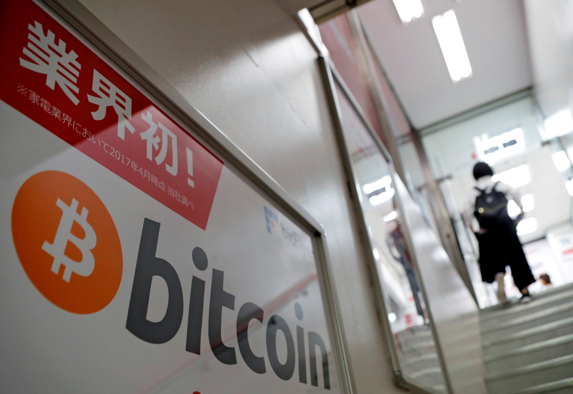 A bitcoin logo is seen on an advertisement of an electronic shop in Tokyo last September. | REUTERS