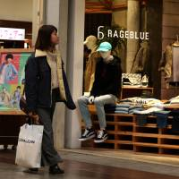 A woman walks past a clothing store in Kobe in February. The economy grew at an annualized rate of 1.6 percent in the October-December quarter, much faster than initially reported, thanks to robust corporate spending in a fresh sign of strengthening domestic demand, the government said Thursday. | BLOOMBERG