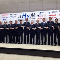 Officials from major domestic automakers and energy companies join hands Monday to mark the creation of joint firm Japan H2 Mobility, which aims to help promote Japan's hydrogen energy goals. | SHUSUKE MURAI