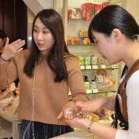Candy Lian (left), a Chinese influencer for cosmetics brands with nearly 2 million followers on Chinese social media platforms such as Weibo and WeChat, tries out a facial cleanser from Japan's House of Rose brand during a live online performance at the Matsuya Ginza department store in central Tokyo in December. | KYODO