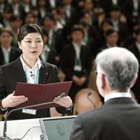 Hiroka Harada, a 22-year-old employee of retailer Ito-Yokado Co., delivers a speech on behalf of this year's 1,071 new employees of the Seven & I Holdings group at a Tokyo hotel Thursday   KYODO