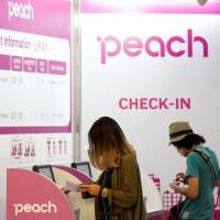 Passengers use Peach Aviation's check-in machines at Narita airport in July 2014. ANA on Thursday said it plans to combine Peach and fellow low-cost carrier Vanilla Air by fiscal 2020. | REUTERS