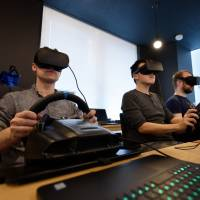 Employees wearing virtual reality headsets use Sony Corp. PlayStation wheel controllers to perform maneuvers within virtual simulations, using Ascent Robotics Inc. Atlas software in Tokyo on Friday. | BLOOMBERG