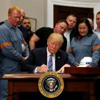U.S. President Donald Trump signs a presidential proclamation placing tariffs on steel and aluminum imports while surrounded by workers from the steel and aluminum industries at the White House in Washington Thursday. | REUTERS