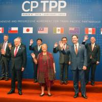 Ministers of the Trans-Pacific Partnership member countries pose for a photo in Santiago Thursday prior to the signing of an agreement without the United States. | KYODO