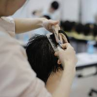 Life skills: While one student photographer had envisioned Tochigi Prison to be filled with rowdy delinquents, he instead found female prisoners hard at work learning skills such as cutting hair. | SEIYA MATSUMURA / VIA KYODO