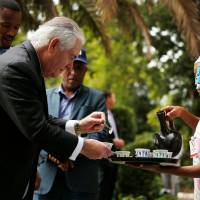 U.S. Secretary of State Rex Tillerson receives a cup of brewed coffee during a traditional coffee ceremony at the U.S. Embassy in Addis Ababa on Thursday. Washington's top diplomat began his first Africa tour by meeting with the African Union chief, who said the continent had moved on from a reported insult by President Donald Trump. | AFP-JIJI
