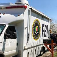 Law enforcement personnel incluing FBI agents are seen near a home that was hit with a parcel bomb in Austin, Texas, Tuesday. | REUTERS