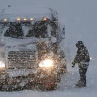 A truck driver prepares to get back on his truck after inspecting it during a snowstorm along Interstate 287 Wednesday in Pompton Plains, New Jersey.   AP