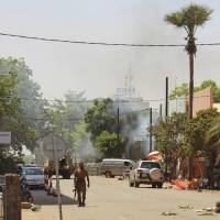 A soldier walks near the army headquarters in central Ouagadougou on Friday after gunfire and explosions rocked Burkina Faso's capital in what the police said was a suspected attack by Islamic extremists. | AP