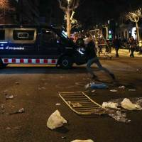 A protestor throws a barrier at a Catalan police van during skirmishes after former regional president Carles Puigdemont was detained in Germany, at a demonstration in Barcelona, Spain, Sunday. | REUTERS