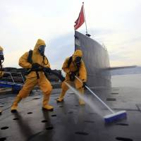 Chinese sailors in protective gear clean and disinfect a nuclear submarine during a drill at the Qingdao submarine base in China's Shandong province in July 2013. | AP