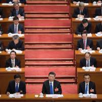 Chinese President Xi Jinping (front center) attends the fourth plenary session of the National People's Congress at the Great Hall of the People in Beijing on Tuesday. | AFP-JIJI
