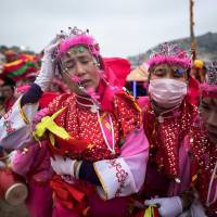 Women from a marching band stand in the wind during a break of a procession at a beach in the village of Fuye on Nanri island in China's Fujian province on Monday. | AFP-JIJI